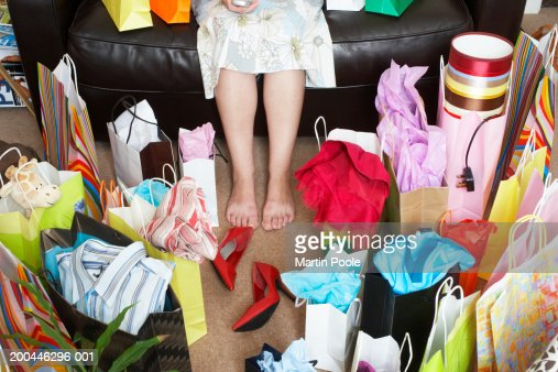 Woman sitting on sofa surrounded with shopping bags