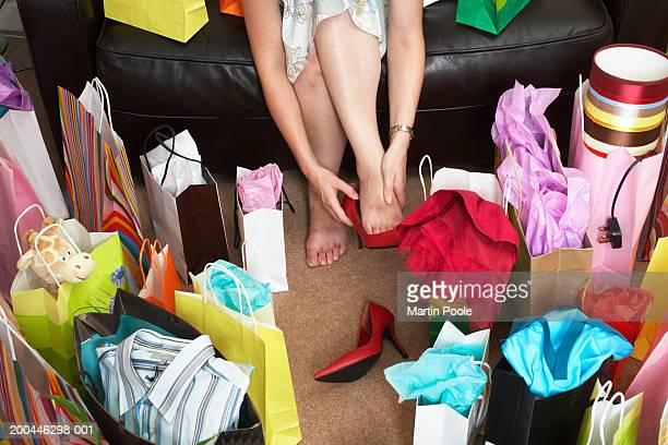 Woman sitting on sofa surrounded with shopping bags, rubbing feet