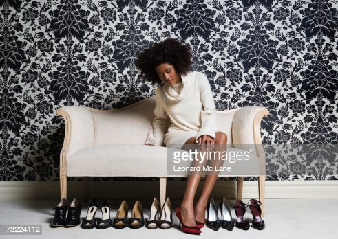 Woman sitting on sofa, trying on shoes : Bildbanksbilder