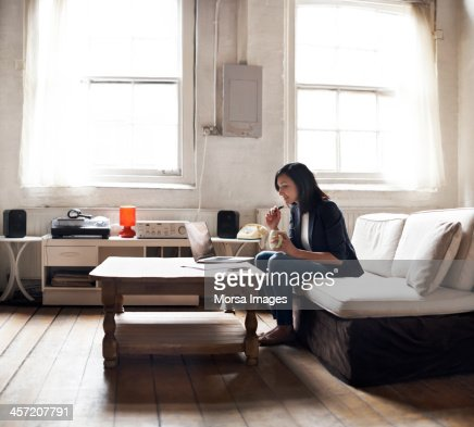 Woman sitting on sofa using laptop : Stock Photo