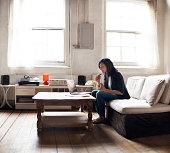 Woman sitting on sofa using laptop