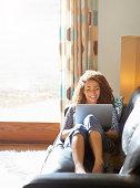 Woman sitting on sofa using laptop.