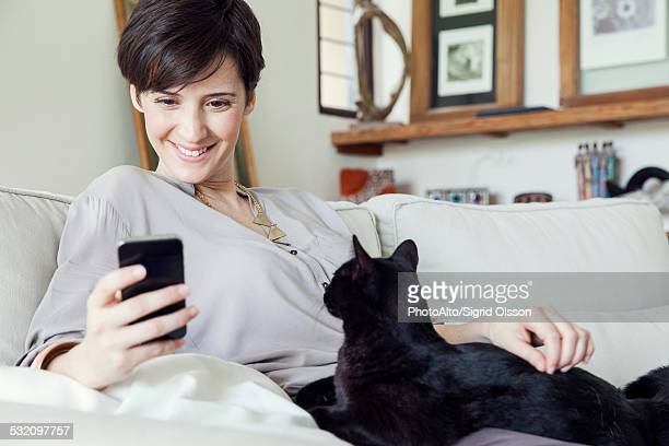 Woman sitting on sofa with cat on her lap, using smartphone