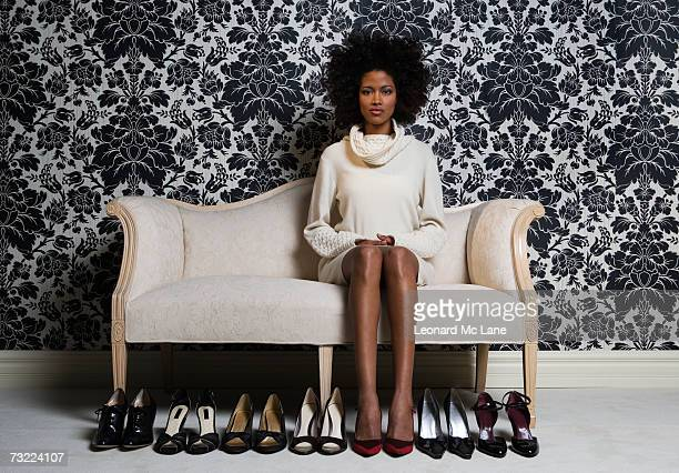 Woman sitting on sofa with pair of shoes on floor, portrait