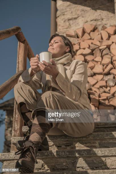 Woman Sitting on Staircase and Drinking Coffee