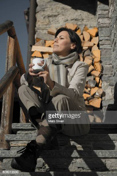 Woman Sitting on Staircase and Drinking Tea