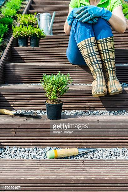 Woman sitting on stairs in garden, resting after gardening works