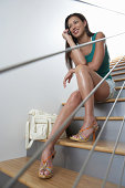 Woman sitting on stairway, talking on cell phone, low angle view