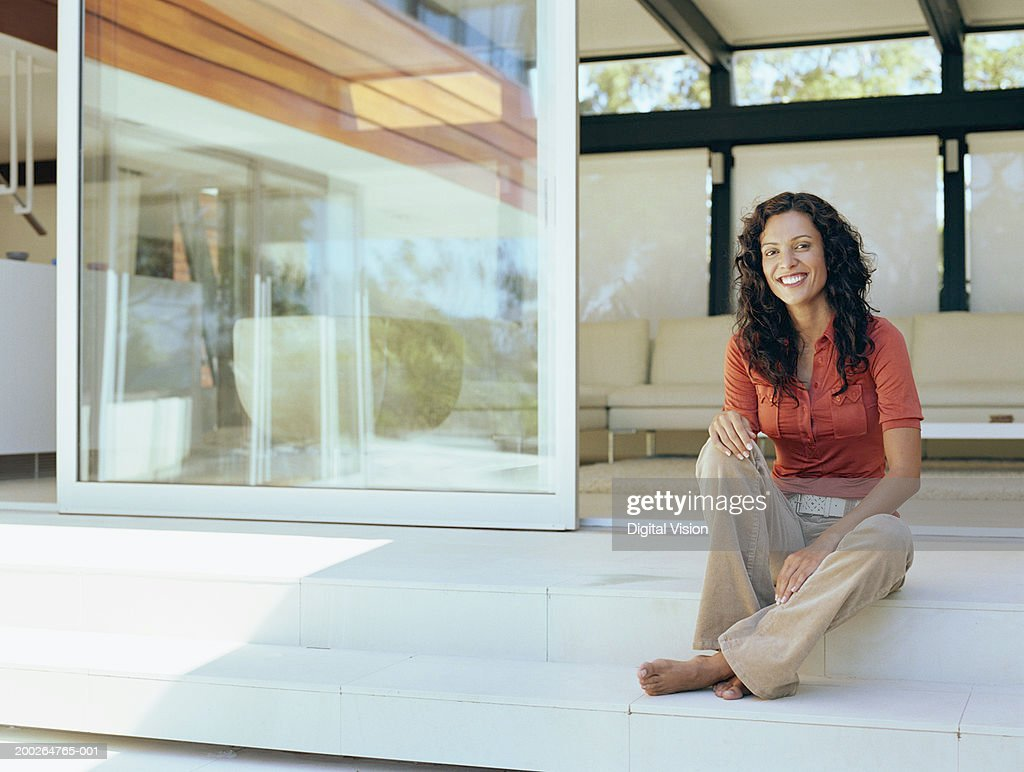 Woman sitting on steps by house, smiling, portrait : Stock Photo