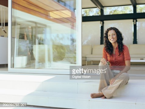 Woman sitting on steps by house, smiling, portrait : Foto stock