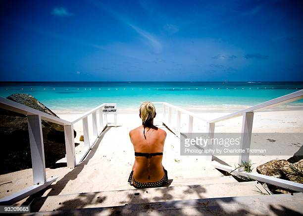 Woman sitting on steps in the carribean in bikini