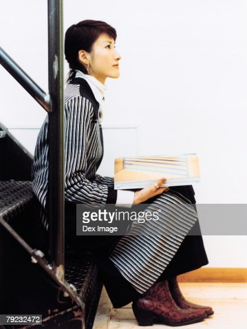 Woman sitting on steps with a book : Stock Photo