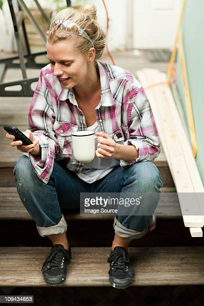 Woman sitting on steps with smartphone