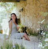 Frau sitzt auf Stein Wand und hältst Wein Glas