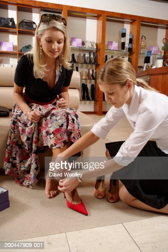 w  sitting on store couch sales assistant fastening shoe strap    w  sitting on store couch   s assistant fastening shoe strap   stock photo