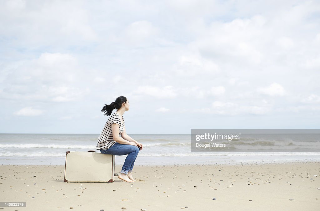 Woman sitting on suitcase, looking out to sea. : Stock Photo