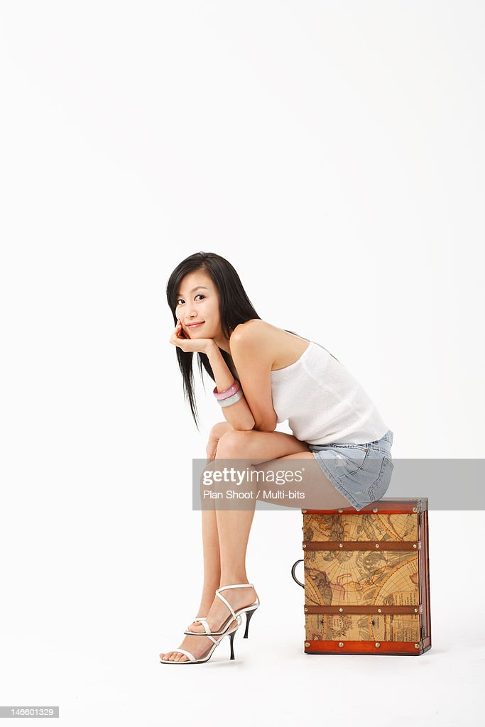 Woman sitting on suitcase
