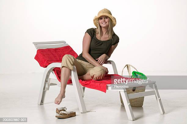 Woman sitting on sun lounger with shopping bag, posing in studio, portrait
