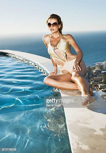 Woman sitting on swimming pool ledge