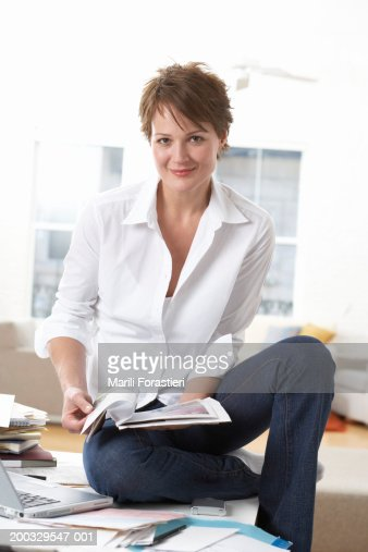 Woman sitting on table, holding magazine, smiling, portrait