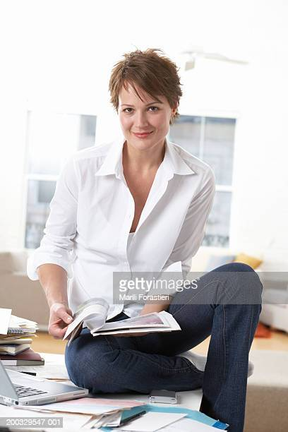 Woman sitting on table, holding magazine, smiling, portrait