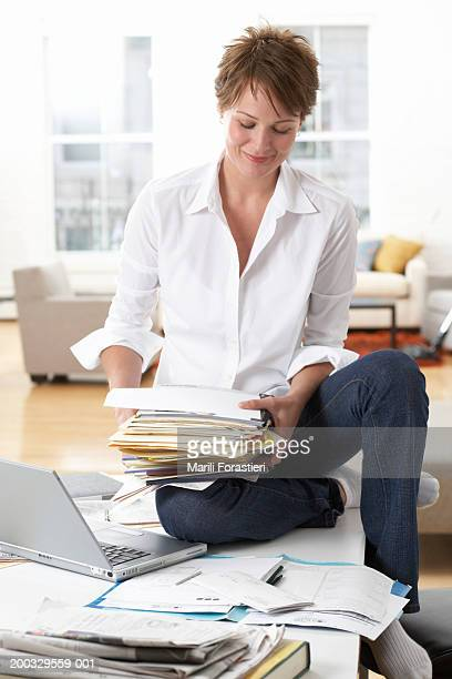 Woman sitting on table, holding papers by laptop, smiling