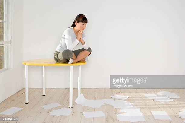 Woman sitting on table with paper on the floor
