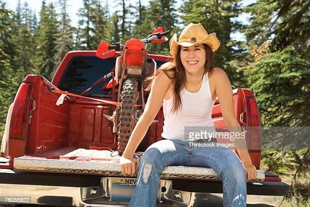 Woman sitting on tailgate with dirt bike