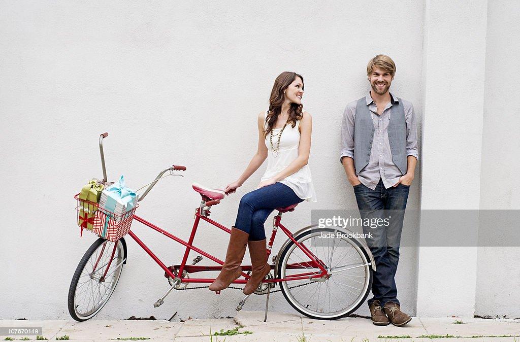 Woman sitting on tandem bike smiling at man : Stock Photo