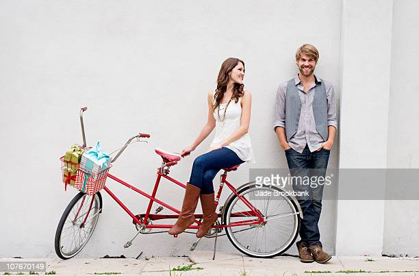 Woman sitting on tandem bike smiling at man