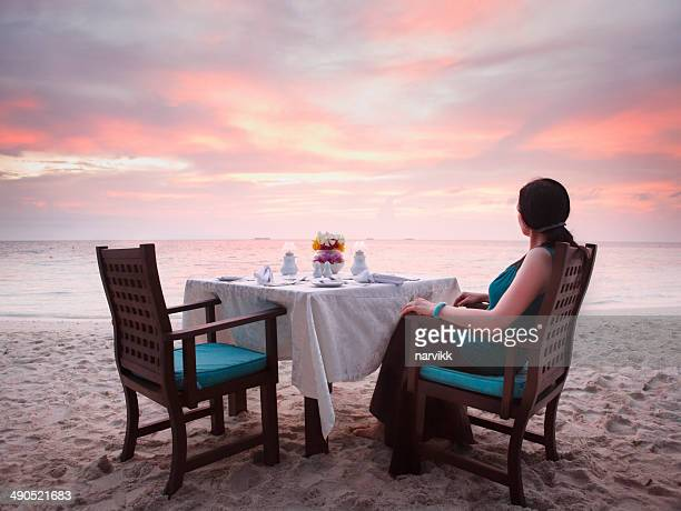 Frau sitzt auf dem Strand von romantischen Sonnenuntergang