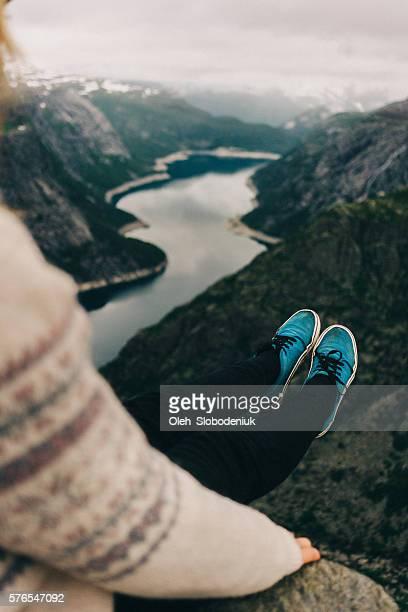 Woman sitting on the edge of Trolltunga