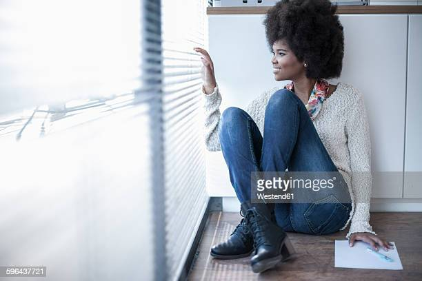 Woman sitting on the floor in office looking out of window