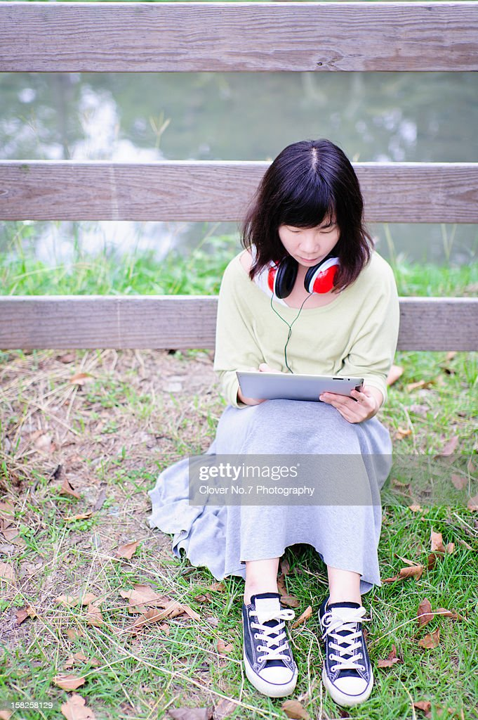 Woman sitting on the grass with a digital tablet : Stock Photo
