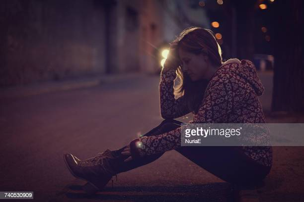 Woman sitting on the pavement at night