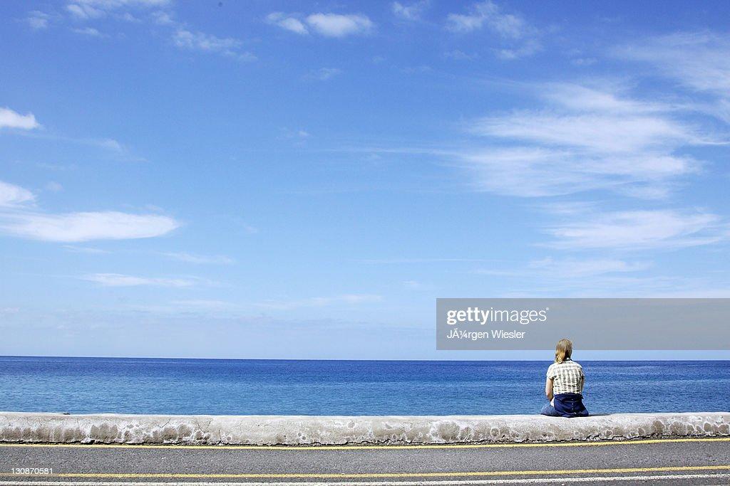 Woman sitting on the pier in La Puntilla, La Gomera, Canary Islands, Spain, Europe