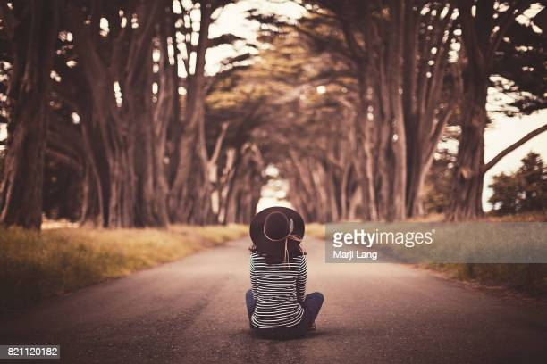 Woman sitting on the road under a Cypress trees tunnel in Point Reyes California USA