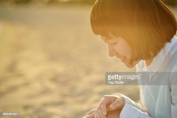 Woman sitting on the sand on the beach