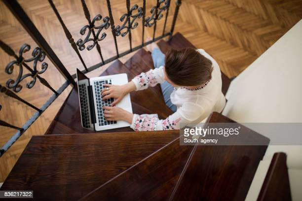 Woman sitting on the steps and using laptop computer