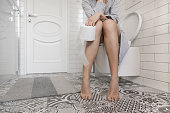 Woman sitting on the toilet holding toilet paper in her hands