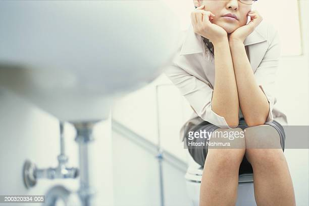 Woman sitting on toilet bowl with hand on chin, mid section