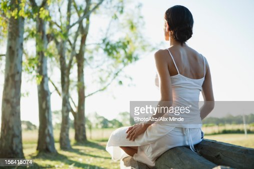 Woman sitting on top of log pile, rear view