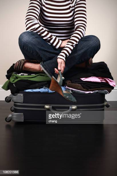 Woman Sitting on Top of Over Packed Suitcase