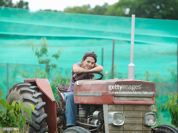 Woman sitting on tractor in orchard