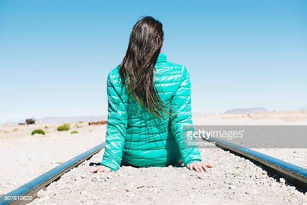 Woman sitting on train tracks in an remote place