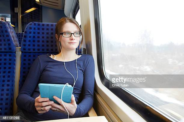 Woman sitting on train with tablet computer