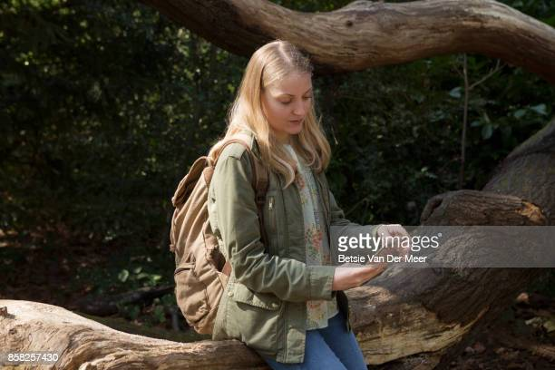Woman sitting on tree trunk in forest, checking her mobile phone.