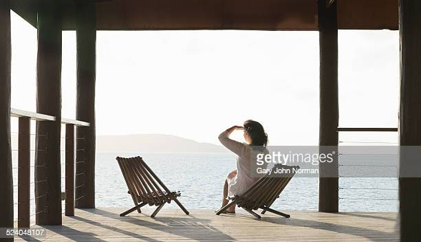 Woman sitting on veranda looking out to sea