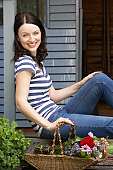 Woman sitting  on veranda with flowers