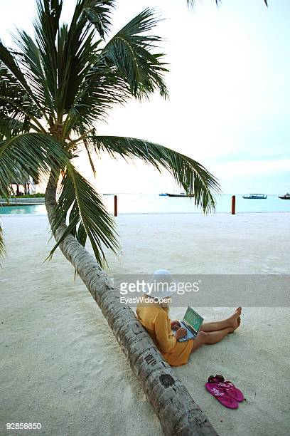 Woman sitting on Villingili beach working with a notebook and mobile phone surfing the internet The island is owned by the luxurious ShangriLa's...
